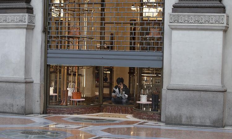 Nhân viên lau dọn ngồi trong một cửa hàng đóng cửa tại khu phố thương mạiVittorio Emanuele ở thành phố Milan, hôm 11/3. Ảnh: AP.