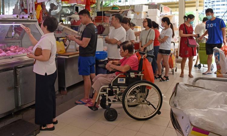 Dân Singapore xếp hàng tại một cửa hàng thịt hôm 22/3. Ảnh: AFP.