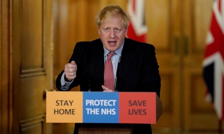 Thủ tướng Anh Borish Johnson trong cuộc họp báo từ xa đầu tiên tại London, Anh, ngày 25/3. Ảnh: Reuters.