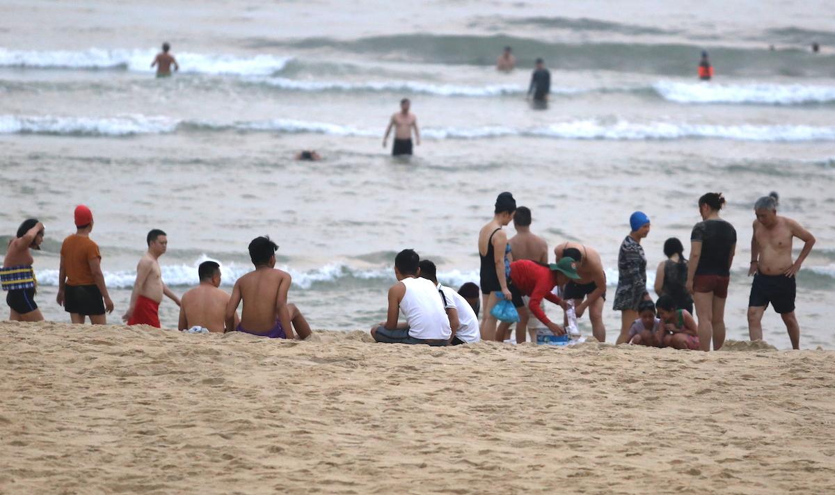 Một nhóm người tụ tập tại bãi biển. Ảnh: Đắc Thành.