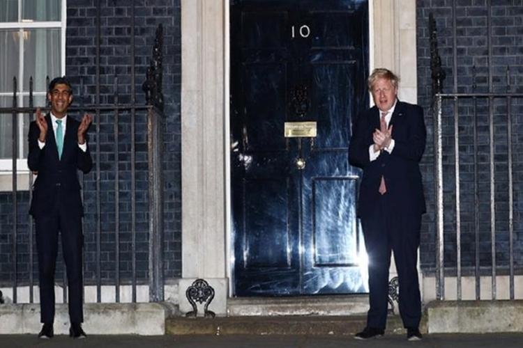 Thủ tướng Boris Johnson (phải) vàBộ trưởng Tài chính Rishi Sunak vỗ tay bên ngoài số 10 phố Downing tối 26/3. Ảnh: Reuters.