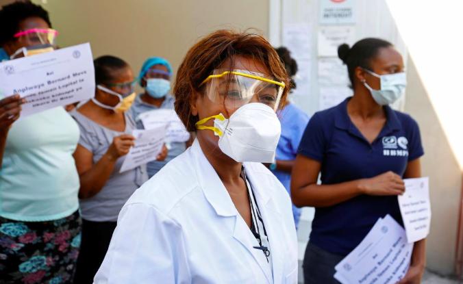 Các nhân viên y tế cầm bảng kêu gọi nhóm bắt cóc thả bác sĩ Jerry Bitar tại bệnh viện Bernard Mevs, thủ đôPort-au-Prince, Haiti hôm 27/3. Ảnh: Reuters