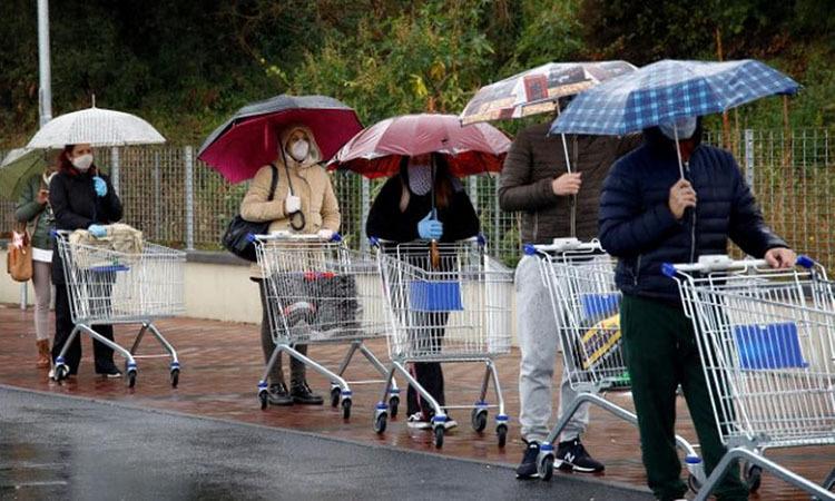 Người dân giữ khoảng cách khi xếp hàng mua đồ bên ngoài một siêu thị ở thành phốCatania, Italy hôm 23/3. Ảnh: Reuters.