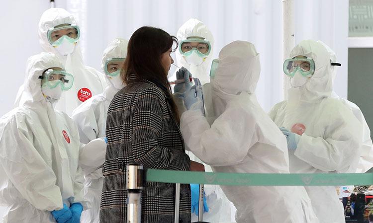 Nhân viên y tế lấy mẫu xét nghiệm cho hành khách tại sân bay Incheon, Hàn Quốc hôm 26/3. Ảnh: Reuters.