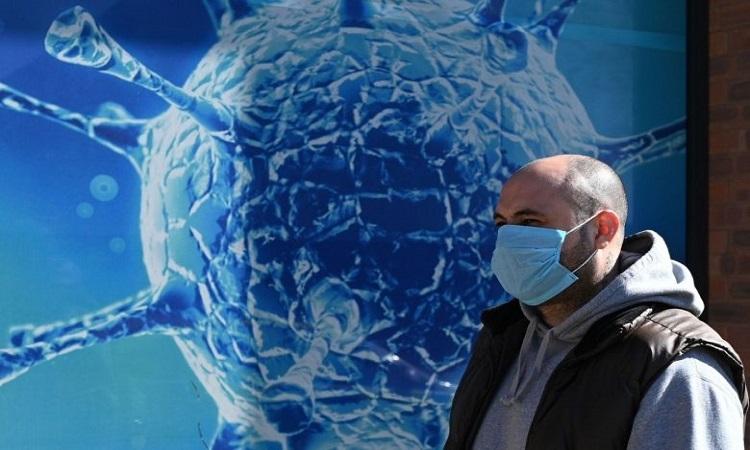 Một người dân đeo khẩu trang đi qua trung tâm khoa học ở thị trấn Oldham, Anh hôm 26/3. Ảnh: AFP.