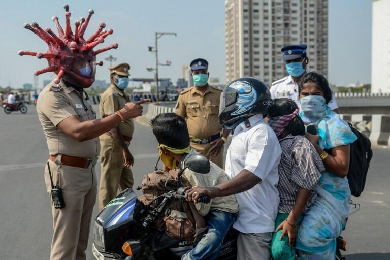 Người dân Ấn Độ nghe cảnh báo từ cảnh sát về dịch Covid-19. Ảnh: Reuters