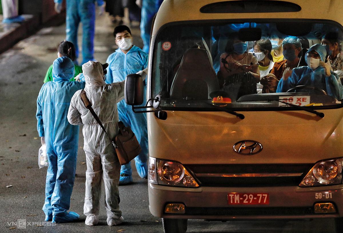Người nhà bệnh nhân ở bệnh viện Bạch Mai lên xe đến khu cách ly tập trung, tối 28/3. Ảnh: Giang Huy
