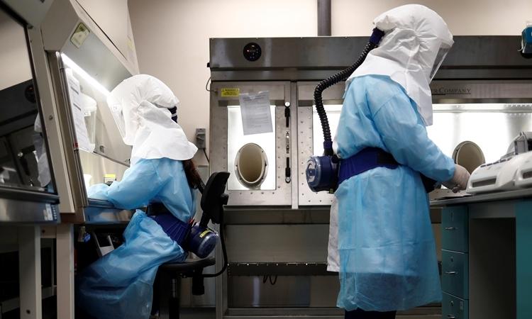 Các nhà khoa học diễn tả quy trình xét nghiệm nCoV trong phòng thí nghiệm tại Singapore hồi đầu tháng ba. Ảnh: Reuters.