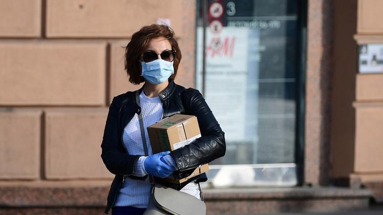 Một phụ nữ đeo khẩu trang và găng tay phòng ngừa nCoV đi trên đường phố Moskva hôm 28/3. Ảnh: Sputnik