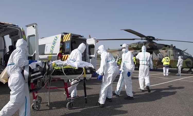 Nhân viên y tế di chuyển một bệnh nhân nhiễm nCoV ở Metz, phía đông nước Pháp, đến Essen, Đức, ngày 28/3. Ảnh: AP.