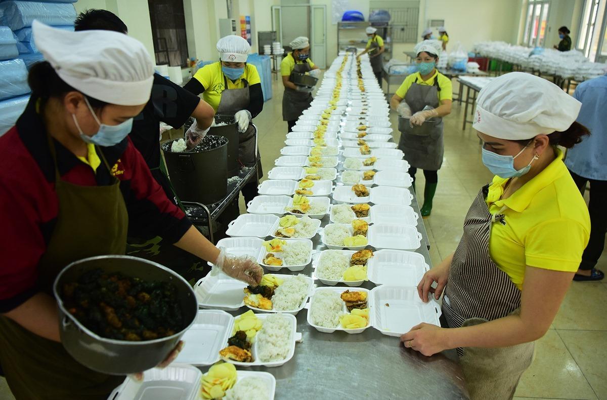 Cán bộ Trung tâm cách ly Trường quân sự Bộ tư lệnh thủ đô chuẩn bị suất ăn cho người bị cách ly, tháng 3/2020. Ảnh: Giang Huy