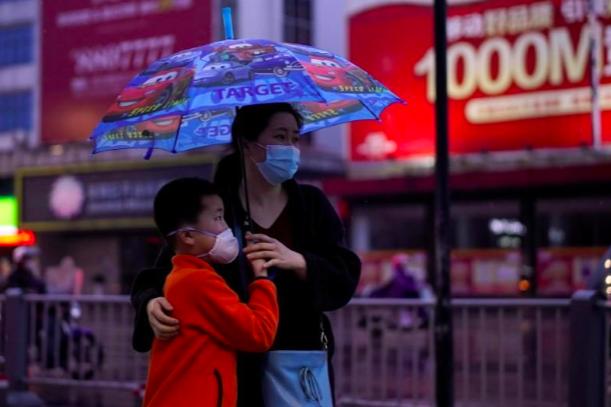 Người dân di chuyển trên đường phố Kinh Châu hôm 26/3, khi lệnh phong toả được nới lỏng ở tỉnh Hồ Bắc. Ảnh: Reuters