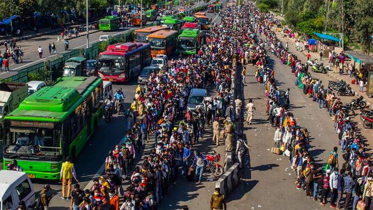 Hàng nghìn lao động nhập cư chờ lên xe buýt về quê sau lệnh phong toả ở ngoại ô New Delhi hôm 28/3. Ảnh: AFP