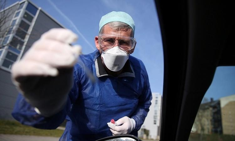 Bác sĩ Đức lấy mẫu xét nghiệm từ một tài xế ởHalle ngày 27/3. Ảnh: AFP.