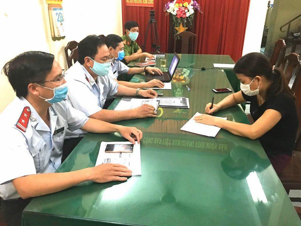 Nhà chức trách tỉnh Thừa Thiên Huế lập biên bản xử phạt người phụ nữ tung tin sai sự thật liên quan đến dịch nCovid. Ảnh: Võ Thạnh