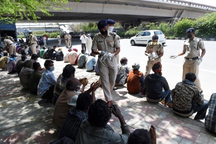 Cảnh sát Ấn Độ phát thực phẩm cho người vô gia cư tại New Delhi hôm 30/3. Ảnh: AFP.