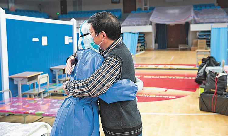 Bệnh nhân Covid-19 ôm tạm biệt nhân viên y tế trước khi xuất viện tại bệnh viện dã chiến Fangcang ở Vũ Xương, thành phố Vũ Hán hôm 10/3. Ảnh:People's Daily.