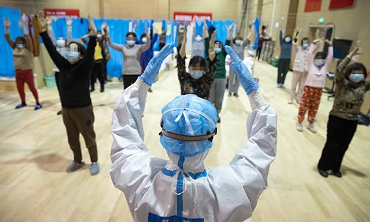 Nhân viên y tế hướng dẫn bệnh nhân Covid-19 tập thể dục tại một bệnh viện dã chiến ở thành phố Vũ Hán hôm 25/2. Ảnh: Xinhua.
