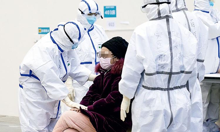 Nhân viên y tế khám cho bệnh nhân Covid-19 tại một bệnh viện dã chiến ở thành phố Vũ Hán hôm 15/2. Ảnh: Xinhua.