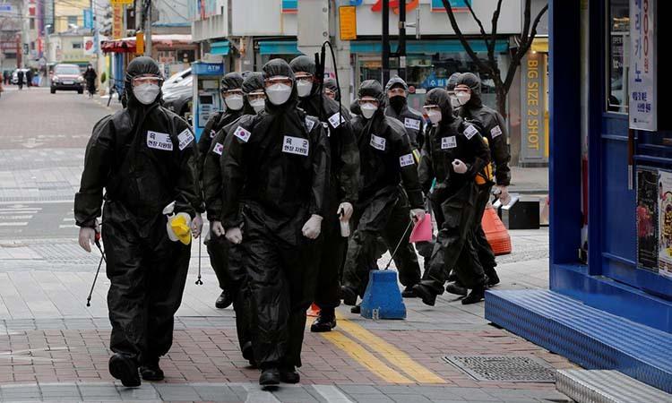 Binh sĩ Hàn Quốc mặc đồ bảo hộ đi khử trùng các tòa nhà hôm 15/3. Ảnh: Reuters.