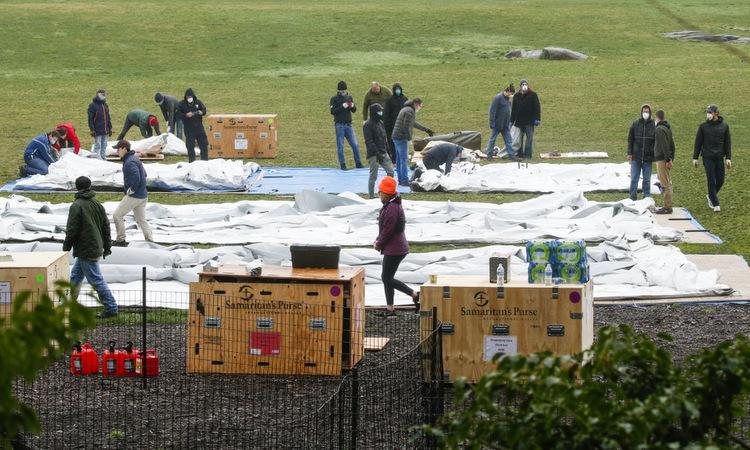 Các tình nguyện viên dựng lều bạt cho bệnh viện dã chiến hôm 30/3. Ảnh: AFP.