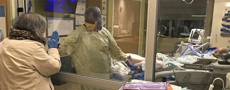 Y tá Judy giúp bà Ty và ông Đinh kết nối với nhau lần cuối qua cửa kính phòng ICU tối 19/3. Ảnh: Seattle Times