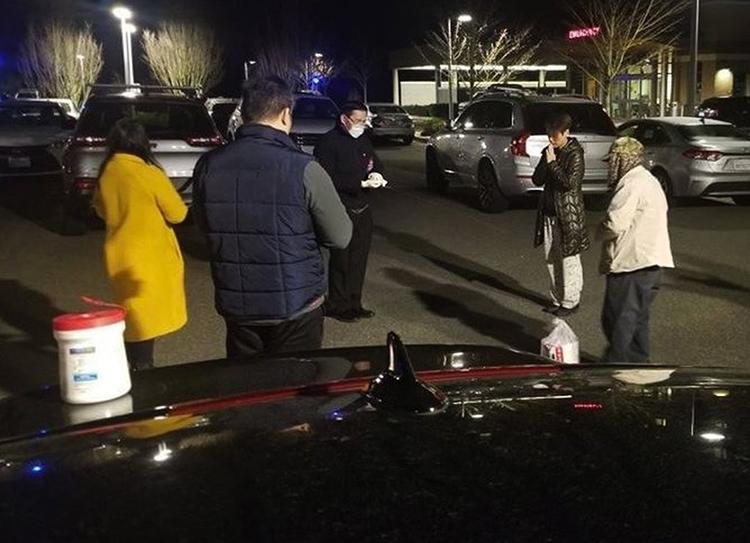 Gia đình ông Đinh cầu nguyện tại bãi đỗ xeTrung tâm Y tế Thuỵ Điển ở thành phốIssaquahtối 19/3 khi ông trong tình trạng nguy kịch. Ảnh: Seattle Times