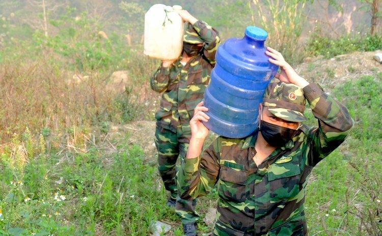 Thiếu tá Đinh Công Vỹ và Tống Hồng Vân ở chốt 168 (2) vác nước hứng từ khe suối nhỏ về lán nấu ăn và sinh hoạt. Ảnh: Hoàng Thuỳ