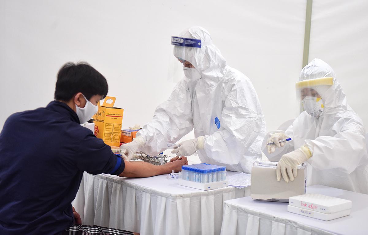 Nhân viên y tế lấy mẫu xét nghiệm nhanh. Ảnh: Giang Huy.