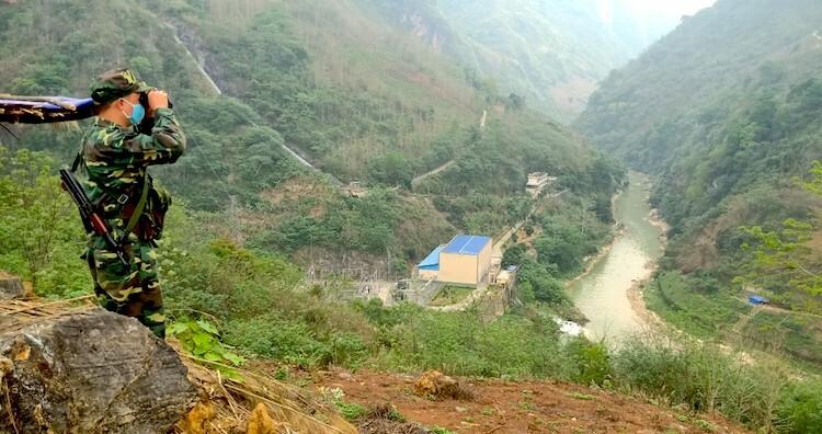 Bộ đội Biên phòng chốt 170 (3) quan sát dọc biên giới, phía dưới là ngã ba sông Xanh - sông Chảy, nơi có nhà máy thuỷ điện của Trung Quốc (ngôi nhà to) và bên kia sông là chốt chặn của đồn Biên phòng Simacai.