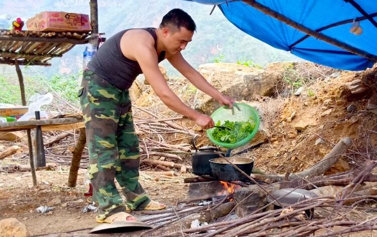 Đại uý Lù A Vinh luộc rau, chuẩn bị bữa cơm cho đồng đội đang gác. Ảnh: Gia Khâu