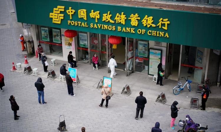 Người dân đeo khẩu trang và giữ khoảng cách cách biệt xã hội tại một ngân hàng ở Vũ Hán, tỉnh Hồ Bắc, Trung Quốc hôm 31/3. Ảnh: Reuters.