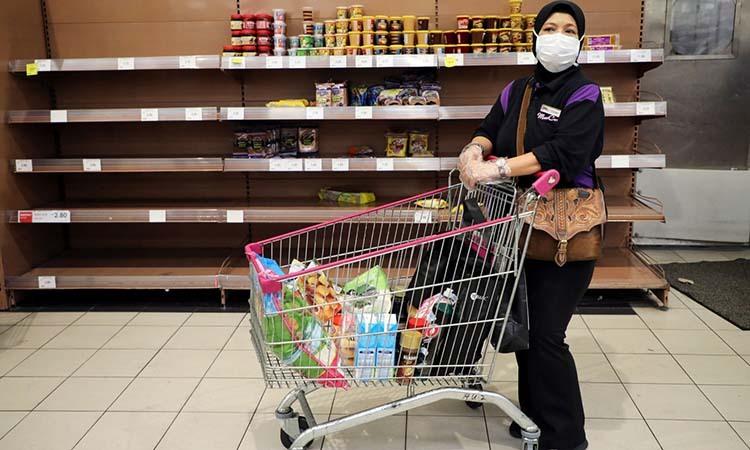 Một phụ nữ đeo khẩu trang tại một siêu thị ở Kuala Lumpur, Malaysia hôm 16/3. Ảnh: Reuters.