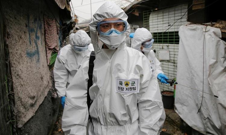 Nhân viên y tế tẩy trùng một khu dân cư ở Seoul, Hàn Quốc, ngày 3/3. Ảnh: Reuters.