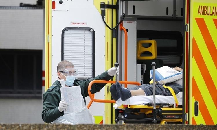 Nhân viên y tế chuyển một bệnh nhân nghi nhiễm nCoV xuống khỏi xe cứu thương tại St Thomas ở London ngày 31/3. Ảnh: AFP.