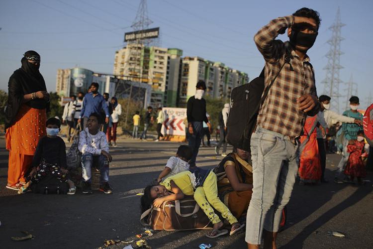 Một gia đình chờ xe về quê giữa lệnh phong toả ở New Delhi, Ấn Độ hôm 28/3. Ảnh: AP