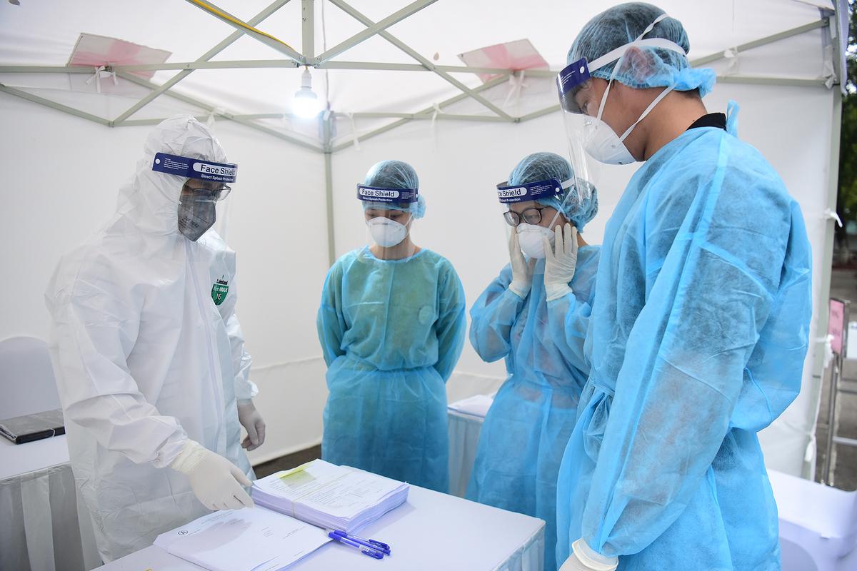 Các nhân viên y tế trạm xét nghiệm nhanh Covid-19 họp bàn phương án lấy mẫu bệnh phẩm người dân sáng 31/3. Ảnh: Giang Huy