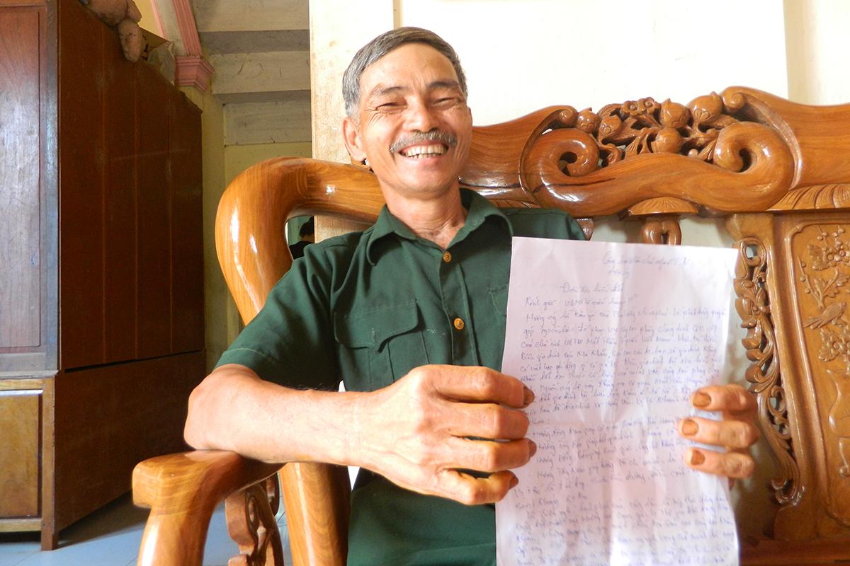 Ông Khoa tươi cười bên lá đơn hiến tặng mảnh đất rộng gần 700m2. Ảnh: Quang Hà