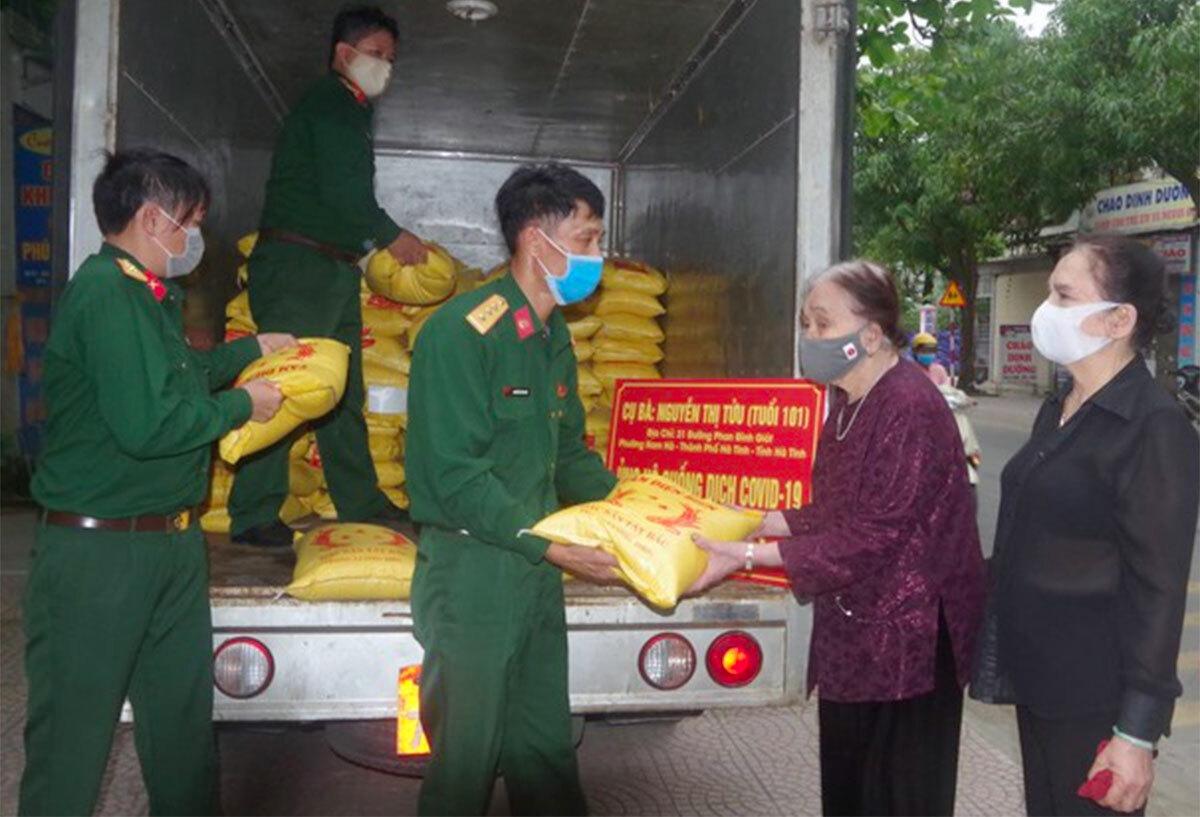 Bà Tửu (thứ hai từ phải sang) trao gạo cho Bộ chỉ huy Quân sự Hà Tĩnh chiều 31/3. Ảnh: Gia Hân