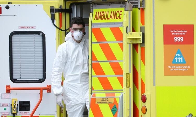 Nhân viên y tế sau một chiếc xe cứu thương ở London, Anh hôm 30/3. Ảnh: Reuters.