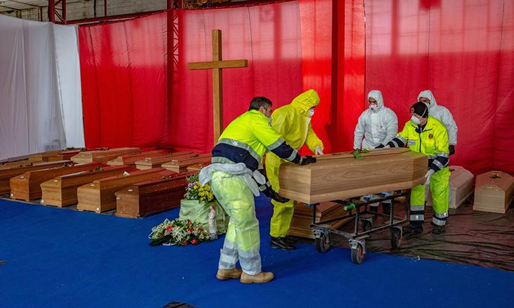 Nhân viên củaCơ quan Bảo vệ dân sự Italy di chuyển quan tài người chết vì Covid-19 ở thành phố Bergamo hôm 31/3. Ảnh: Bloomberg News.