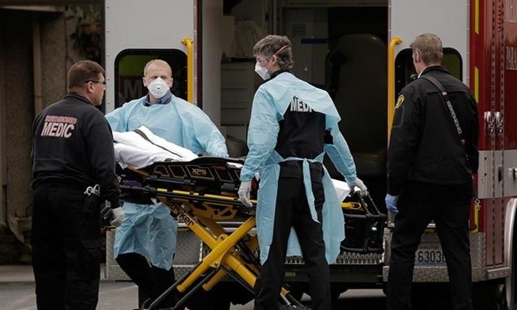 Nhân viên y tế Mỹ di chuyển bệnh nhân Covid-19 lên cáng cứu thương ở bang Washington đầu tháng này. Ảnh: Reuters.