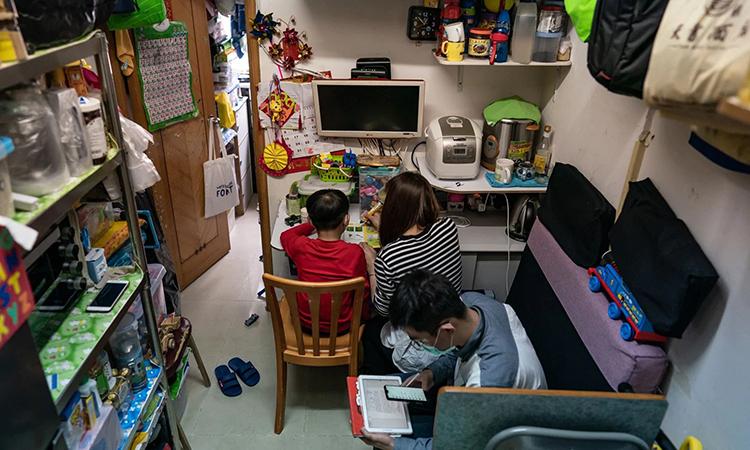Tang Yi Han (giữa) và hai con trai chen chúc trong căn hộ hơn 10 m2 ở Hong Kong hôm 22/3. Ảnh: Washington Post.
