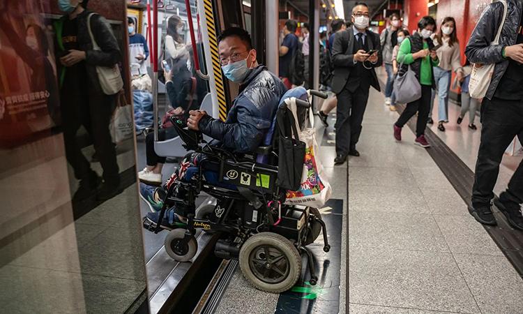 Jacky Chan ngồi xe lăn lên tàu điện ngầm ở Hong Kong hôm 19/3. Ảnh: Washington Post.