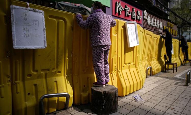 Người dân Vũ Hán đứng lên ghế để mua hàng hóa qua hàng rào phong tỏa ngày 1/4. Ảnh: Reuters.