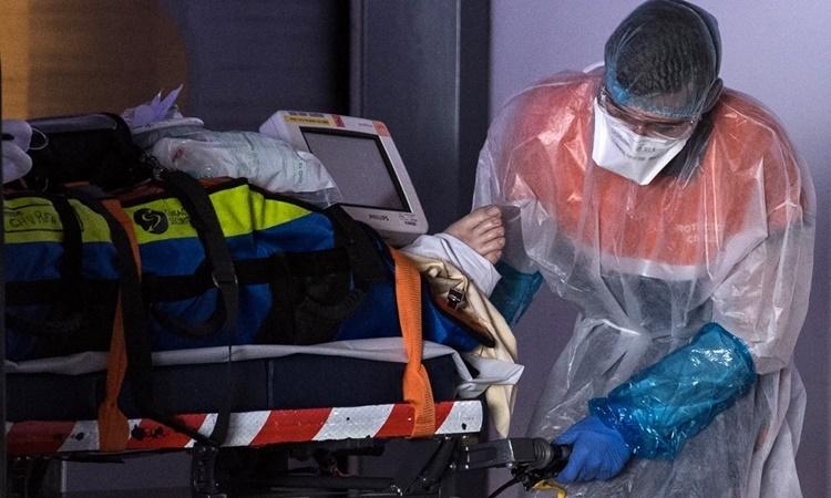 Nhân viên y tế di chuyển bệnh nhân nhiễm nCoV tới một bệnh viện ở Paris, Pháp, ngày 1/4. Ảnh: AFP.