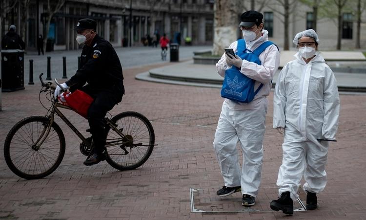 Người Trung Quốc mặc đồ bảo hộ trên đường phố Vũ Hán ngày 1/4. Ảnh: AFP.