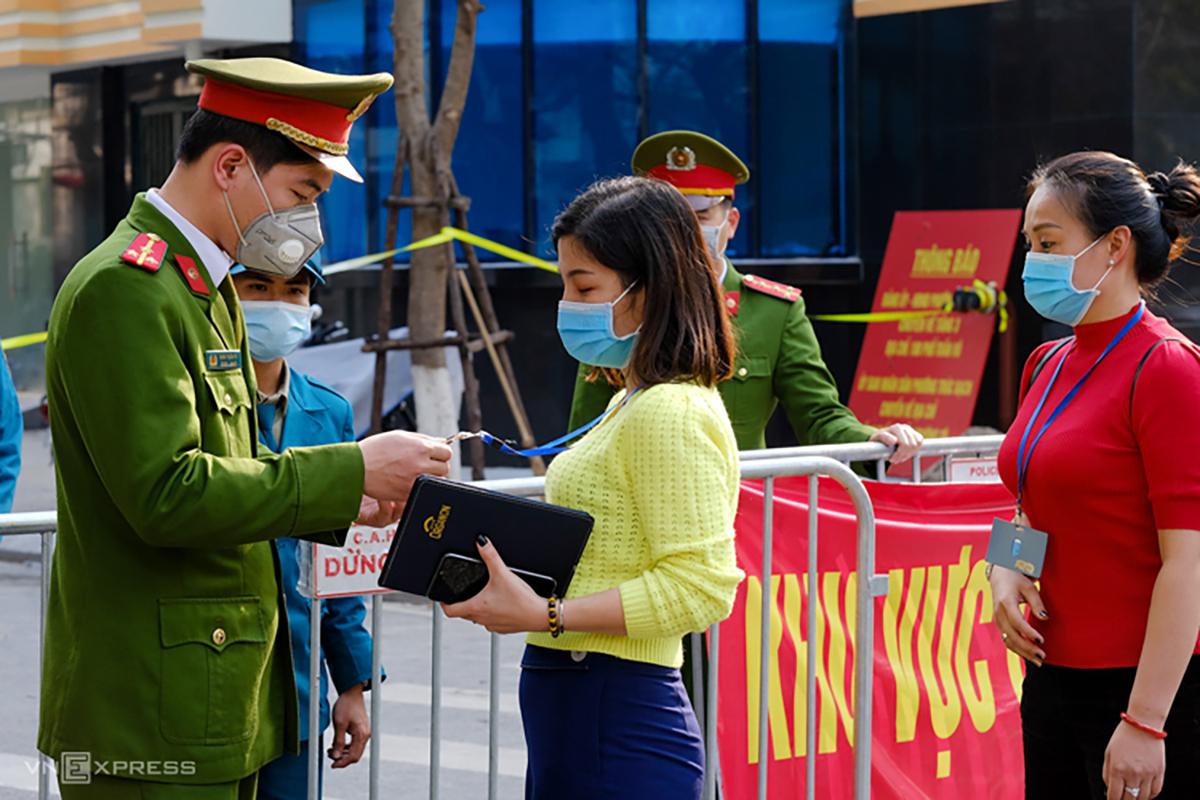 Cảnh sátkiểm tra người làm nhiệm vụ tạiphố Trúc Bạch hôm 9/3. Ảnh: Giang Huy