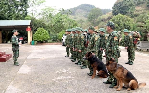 Bộ đội biên phòng cùng chó chiến đấu nghe phổ biến trước khi thực hiện nhiệm vụ. Ảnh: Biên phòng