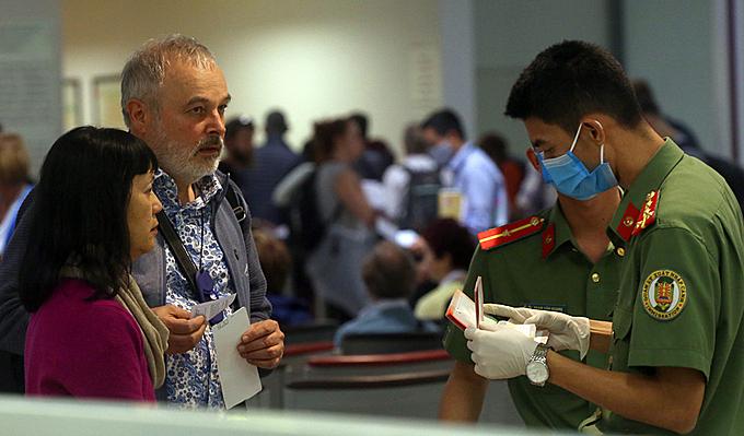 KIểm soát viên nhập cảnh cửa khẩu Nội Bài đeo găng tay, khẩu trang, khi hướng dẫn, làm việc, tiếp xúc với người nước ngoài hôm 11/3. Ảnh: Bá Đô